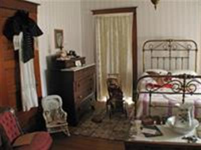 A wire frame bed and historic furniture inside another bedroom in the Yost House.