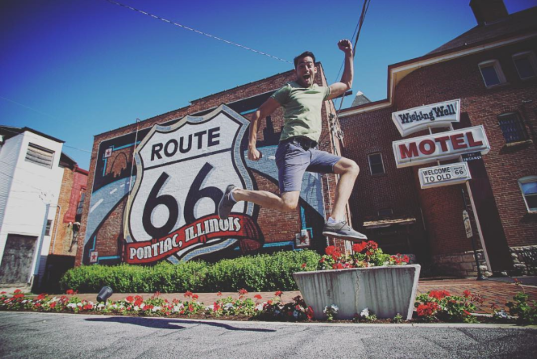 Man jumping in front of Pontiac Route 66 Mural