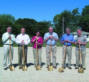 Men standing with shovels at a ground breaking ceremony.